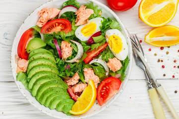 Delicious fish salad (salmon or tuna) with lettuce, tomatoes, red onion, eggs and avocado with dressing of olive oil , mustard and spices. Light dinner. Selective focus