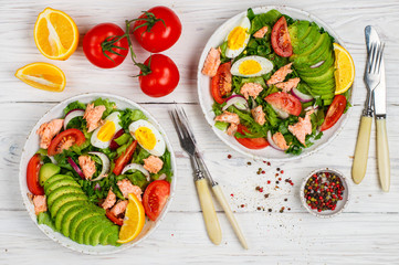 Two servings of Delicious fish salad (salmon or tuna) with lettuce, tomatoes , red onion, eggs and avocado with dressing of olive oil , mustard and spices. Light dinner. Selective focus