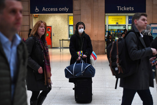 A woman wearing a face mask at London Waterloo Station during rush hour as the number of coronavirus cases grow around the world