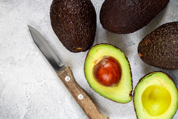 Whole and cut in half ripe organic avocados and a knife on a grey  background. The Haas Avocado. Source of vitamins , trace elements , beta-carotene and omega-3 fatty acids . Healthy food, diet
