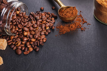 Fotobehang - Roasted coffee beans and ground coffee on black table