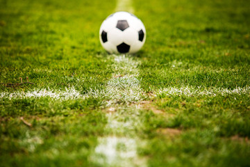Classic soccer ball, typical black and white pattern, placed on the white marking line of the...