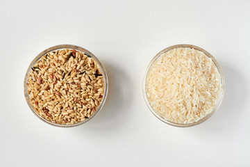Raw brown rice and white rice in a transparent glass plate on white background. Problem of choice. Closeup, top view