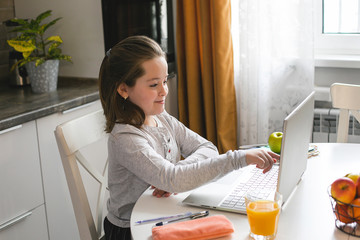 Pretty cute schoolgirl studying at home using laptop. Coronavirus home school, online education, home education, quarantine concept
