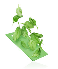 Spinach leaves fall on a kitchen board on a white background