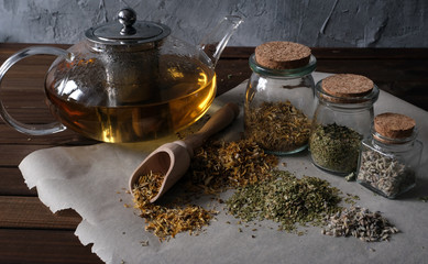 Homemade apothecary. Natural herbs medicinal. Dried herbs in glass jars and teapot on dark wooden surface. Various kinds of herbal tea.