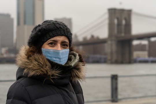 Woman wearing surgical mask with warm clothes in Dumbo neighborhood.Concept of Coronavirus, COVID-19 and quarantine