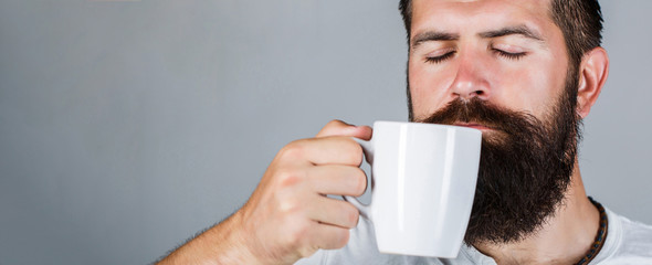 Portrait male. Closeup tea. Good morning, man holding a cup tea. Morning concept. Handsome bearded male holds cup of coffee, tea. Smiling hipster man with cup of fresh coffee