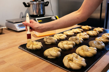 Close up person brushing cinnamon buns on a baking tray in an artisan bakery.