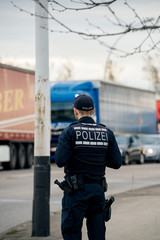 Rear view of unrecognizable German Polizei Police officer inspecting the border crossing in Kehl from France Strasbourg during crisis measures novel coronavirus