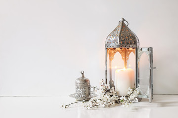 Obraz Silver decorative cup of tea, white flowers, prunus tree blossoms and glowing Moroccan lantern on table background. Iftar dinner. Ramadan Kareem greeting card, invitation. Eid ul Fitr muslim holiday. - fototapety do salonu