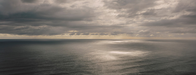 Storm clouds clearing over expansive ocean, dappled sunlight on water, northern Oregon coast,Clearing storm clouds and dappled sunlight on vast ocean at dusk Fotobehang
