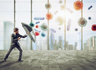 Businessman with umbrella covers himself from bacteria. Concept of solution to stop viruses...