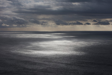 Storm clouds clearing over expansive ocean, dappled sunlight on water, northern Oregon coast,Clearing storm clouds and dappled sunlight on vast ocean at dusk