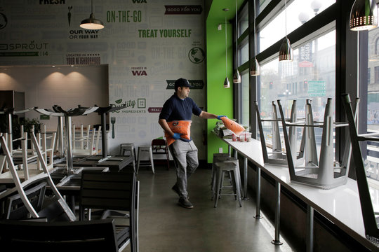 Co-owner of Sprout, Michael Kelly, lays out food to give away from the restaurant's refrigerator that will otherwise spoil while the restaurant is closed, as authorities restrict all dining inside restaurants due to reports of coronavirus disease (COVID-