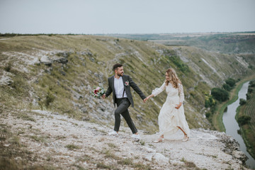Smiling bride and groom spending time together. Posing on the mountain hills background. Dressed in white dress beautiful blonde caucasian bride and handsome groom. Hugs, kissess and enjoy the company