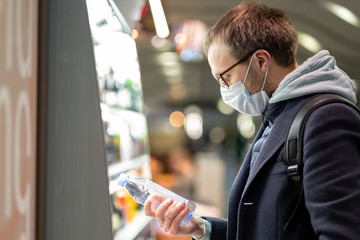Caucasian man customer in glasses wearing facial protective mask, buying and choosing water bottle, reads information on a label. Purchase of food during the coronavirus, covid-19 epidemic in USA.