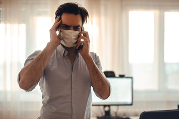 Stressful news over the phone for the young corporate freelancer wearing a protective mask, home quarantine