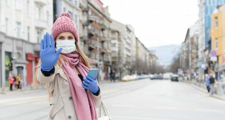 Woman wearing corona mask giving stop sign towards camera Fototapete
