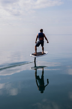 Man riding an electric hydrofoil foil board on a lake with a life jacket