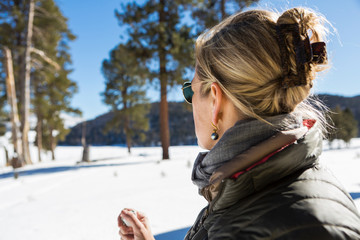 A woman looking at a beautiful snow landscape with pine trees.,Valle Caldrea