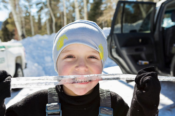Smiling six year old boy with a long icicle in his mouth,Valle Caldrea