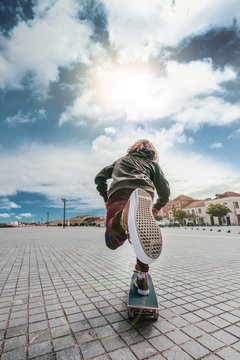 Vertical picture of a skateboarder under the sunlight and a cloudy sky at daytime