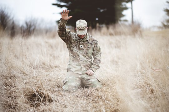 American soldier kneeling in despair on a grass field with his hand raised above