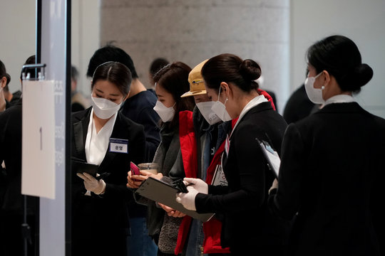 Employees wearing masks to prevent contracting the coronavirus lead shareholders of Samsung Electronics Co. before the company's annual general meeting in Suwon