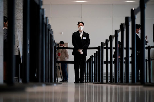 An employee wearing a mask to prevent contracting the coronavirus waits for a shareholder of Samsung Electronics Co. before the company's annual general meeting in Suwon