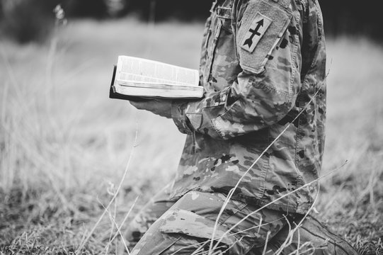 Grayscale shot of a young soldier kneeling while holding an open bible in a field