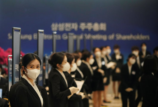 Employees wearing masks to prevent contracting the coronavirus wait for a shareholder of Samsung Electronics Co. before the company's annual general meeting in Suwon