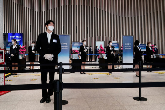 Employees wearing a mask to prevent contracting the coronavirus wait for a shareholder of Samsung Electronics Co. before the company's annual general meeting in Suwon