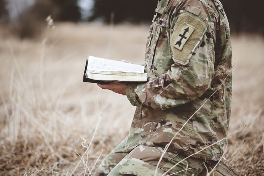 Shallow focus shot of a young soldier kneeling while holding an open bible in a field