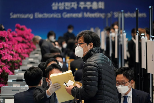 A shareholder of Samsung Electronics Co. wearing a mask to prevent contracting the coronavirus arrives for the company's annual general meeting in Suwon