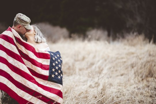 Shallow focus shot of an American soldier kissing his loving wife while wrapped in an American flag