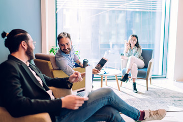 Cheerful coworkers communicating in bright lounge