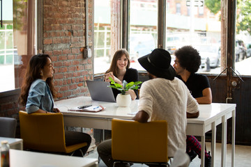 Multi-ethnic executives discussing at desk in coworking space