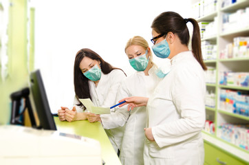 Happy positive pharmacists with surgical masks on face organizing theirs work day