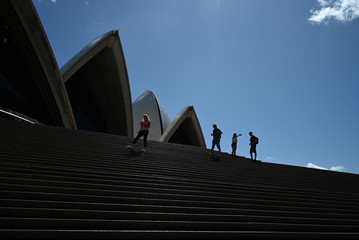 A handful of tourists stand atop the mostly deserted steps of the Sydney Opera House in Sydney