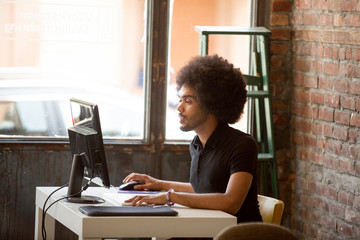 Businessman with afro hair using computer at desk in office