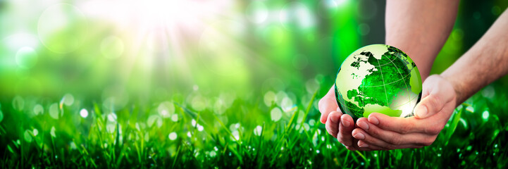 Hands Holding Crystal Earth In Lush Green Environment With Sunlight - Caring For The Environment Concept Wall mural