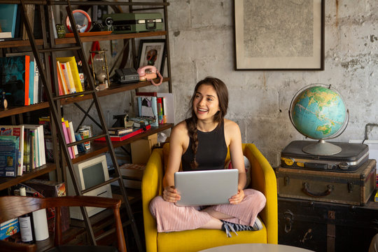 Smiling businesswoman with laptop computer looking away while sitting on armchair at creative office
