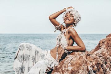 cheerful young stylish woman wearimg turban on the beach