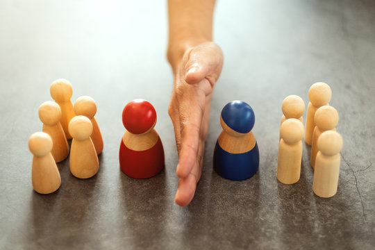 Concept image of a business woman separate wooden people into two group