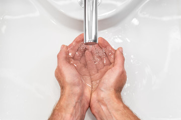 Wash hands with soap hand hygiene for coronavirus corona virus spread prevention. Top view of male hands rubbing under water.