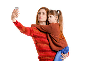 Mother and her little daughter taking selfie on white background