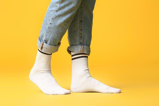 Male legs in socks and jeans on color background