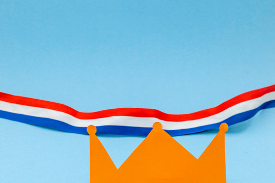 King's day image for the Dutch fest of Koningsdag with an orange paper crown and a red white and blue ribbon