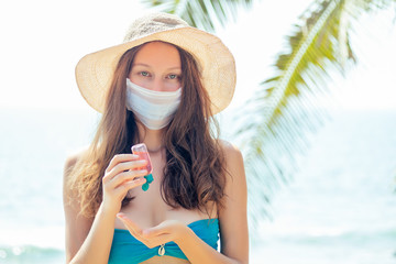 woman wearing mask in tropical beach useing antibacterial gel on hands. prevention corona-virus concept
